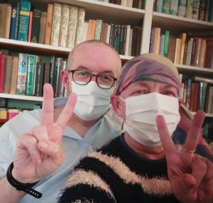 Two older people wearing medical facemasks and giving a victory sign