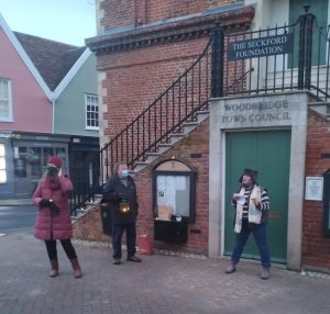 Three people - very distanced - in front of ancient brick building. Two are masked. The third - Caroline Page - is speaking