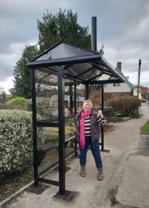 Caroline Page standing looking very pleased in a clearly new bus shelter with the ancient, yellow Cherry Tree inn behind her