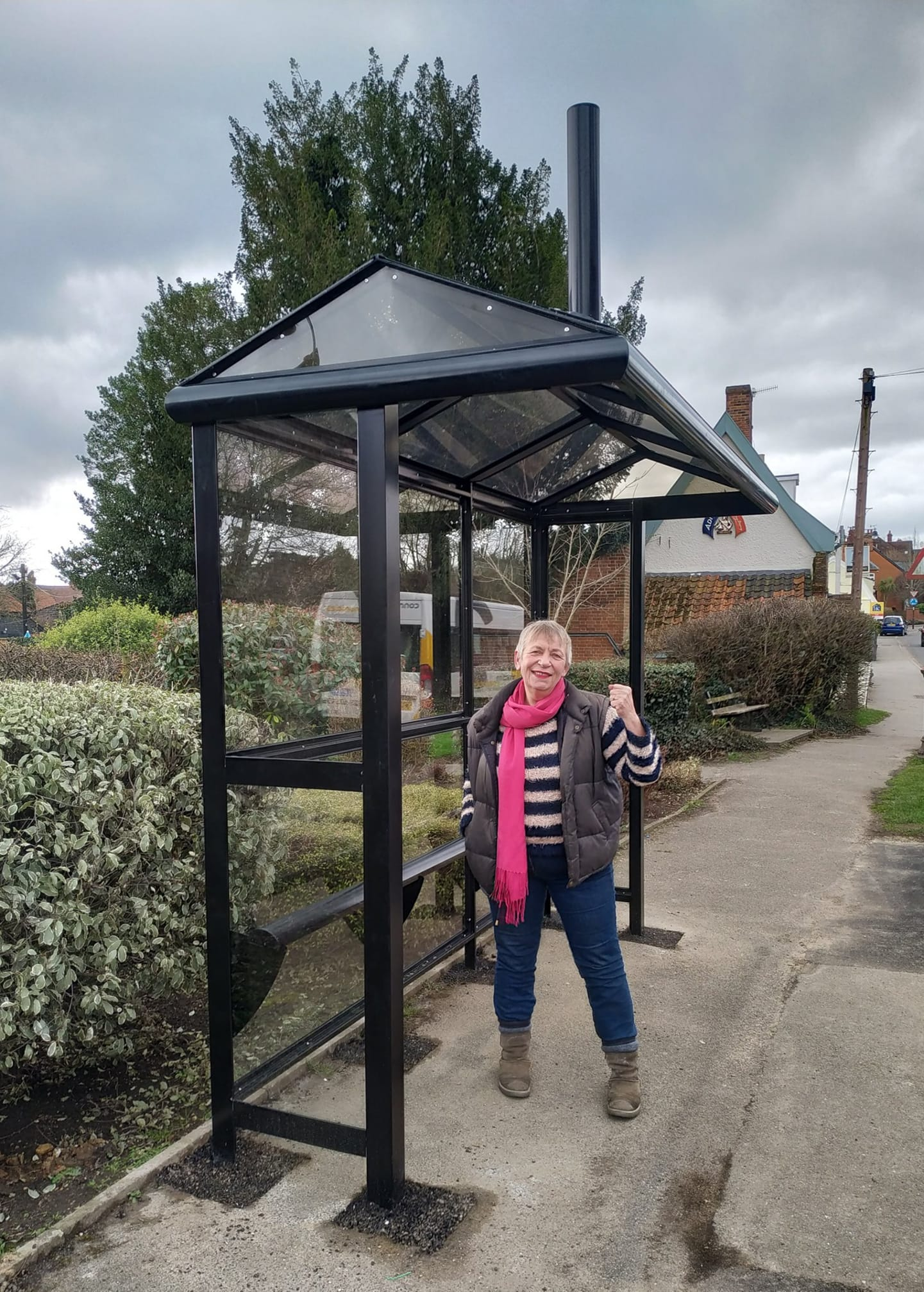 Caroline Page standing very pleased in a clearly new bus shelter with the ancient, yellow Cherry Tree inn behind her